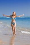 De jonge bevallige vrouw gaat op kust van oceaan stock foto
