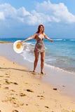 De jonge bevallige vrouw gaat op kust van oceaan royalty-vrije stock afbeeldingen