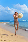 De jonge bevallige vrouw gaat op kust van oceaan stock afbeelding