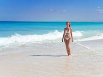 De jonge bevallige vrouw gaat op kust van oceaan stock afbeeldingen
