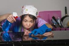 De jonge bezige Aziatische Koreaanse vrouw in hoofdsjaal en was gloves het gebruiken van nevelfles het schoonmaken huiskeuken in  royalty-vrije stock foto