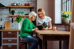 De jonge Bijbel van de kerk vrijwilligerslezing met gepensioneerde thuis keuken royalty-vrije stock afbeeldingen