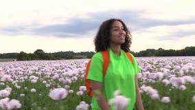 De jonge biracial vrouw wandeling met oranje rugzak op weg door gebied van roze papaver bloeit stock video