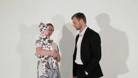 De jonge blauw-eyed man in kostuum danst met vrouw die baby in handen houdt stock videobeelden