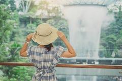 De jonge blauwe kleding van de vrouwenslijtage en hoed, Aziatische reiziger die en zich aan mooie regendraaikolk Juweelchangi Luc stock fotografie