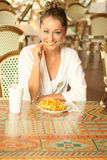 De jonge blonde eet sommige gebraden gerechten Royalty-vrije Stock Foto's