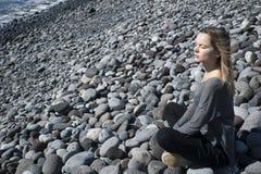 De jonge blonde Kaukasische vrouwelijke zitting in het ontspannen, mediterend positie met ogen sloot, dragend een neutrale uitrus Royalty-vrije Stock Foto's