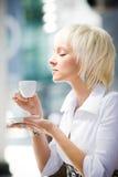 De jonge blonde kop van de vrouwenholding en proevende koffie Royalty-vrije Stock Foto's