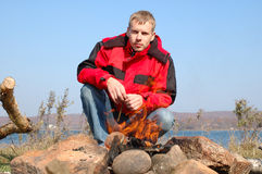 De jonge blonde mens in rood jasje zit dichtbij brand. Stock Fotografie