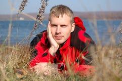 De jonge blonde mens in rood jasje zit op de kust. Stock Fotografie