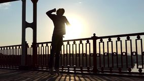 De jonge Blonde Mens spreekt door Mobiel en springt gelukkig bij Zonsondergang in slo-Mo stock videobeelden