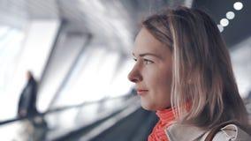 De jonge blonde vrouw berijdt op travelator stock videobeelden