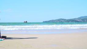 De jonge blonde vrouw met blauwe bikini en strohoed zit op het strand en bekijkt het overzees stock footage