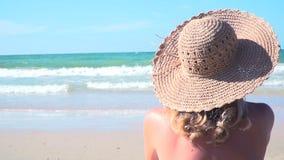 De jonge blonde vrouw met blauwe bikini en strohoed zit op het strand en bekijkt het overzees stock videobeelden