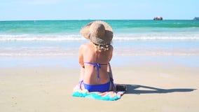 De jonge blonde vrouw met blauwe bikini en strohoed zit op het strand en bekijkt het overzees stock video