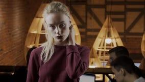 De jonge blonde vrouw raakt haar haar in modieus restaurant stock videobeelden