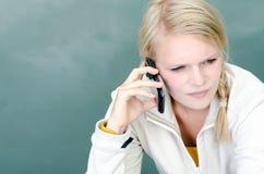 De jonge blonde vrouw riep met haar Smartphone op Stock Fotografie