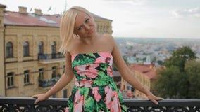 De jonge blonde vrouw stelt fotograaf openlucht stock footage
