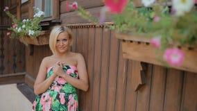 De jonge blonde vrouw stelt fotograaf openlucht stock video