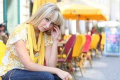 De jonge blonde vrouw zit voor sidewal Royalty-vrije Stock Fotografie