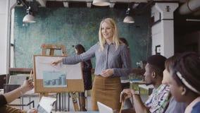 De jonge blonde vrouwelijke manager motiveert gemengde rascollega's om te werken De teamleider legt financiële gegevens op zolder stock foto