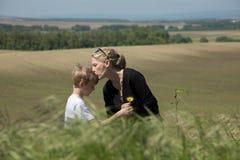De jonge blondejongen geeft bloem aan zijn moeder met liefde In openlucht, natuurlijke scène Royalty-vrije Stock Foto
