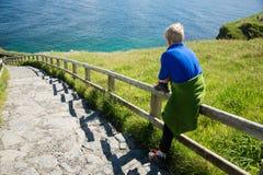 De jonge blondejongen zit en wacht op een houten omheining, naast stappen, bij Ierse kust Royalty-vrije Stock Fotografie