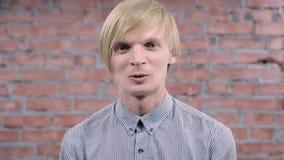 De jonge blondemens die en spreekt op camera glimlachen rocking Bakstenen muur auditie stock videobeelden