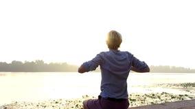 De jonge blondemens zit en heft zijn handen op riverbank bij zonsondergang in slo-mo op stock videobeelden