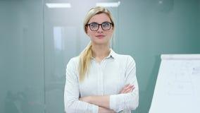 De jonge blondeonderneemster in bureaukleren en glazen bekijkt camera en het glimlachen stock video
