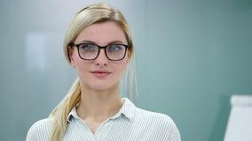 De jonge blondeonderneemster in bureaukleren en glazen bekijkt camera en het glimlachen stock videobeelden