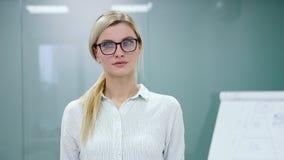 De jonge blondeonderneemster in bureaukleren en glazen bekijkt camera en het glimlachen stock footage