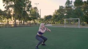De jonge blondevrouw die hurkende sprongenoefening op voetbalgebied doen in park, ochtend werkt uit stock videobeelden