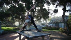 De jonge blondevrouw doet yogaoefeningen op de lijst in het bos stock videobeelden