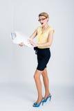 De jonge blondevrouw gaat met handelspapieren Stock Foto's