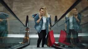 De jonge blondevrouw in jeansjasje glimlacht het uitgaan op de roltrappen in het winkelcomplex stock videobeelden