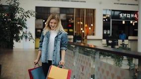 De jonge blondevrouw in jeansjasje loopt rond een winkelcomplex met kleurrijke zakken stock video