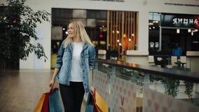 De jonge blondevrouw in jeansjasje loopt rond een winkelcomplex met kleurrijke zakken stock footage