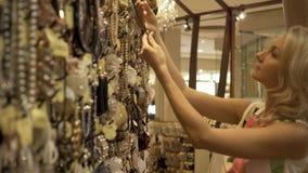 De jonge blondevrouw kiest bijouterie in juwelen in de winkel stock footage