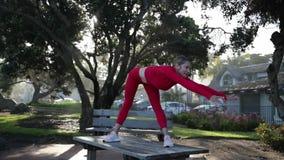 De jonge blondevrouw in rood latexkostuum doet yogaoefeningen op de lijst in het bos stock video