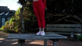 De jonge blondevrouw in rood latexkostuum doet yogaoefeningen op de lijst in het bos stock footage