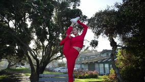 De jonge blondevrouw in rood latexkostuum doet yogaoefeningen op de lijst in het bos stock videobeelden