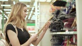 De jonge blondevrouw selecteert hanger voor garderobe in een supermarkt stock videobeelden