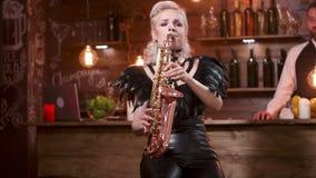 De jonge blondevrouw in sexy leerkleren voert een lied op een saxofoon uit stock footage
