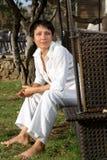 De jonge blootvoetse vrouw kleedde wit zit op bank Stock Fotografie