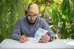 De jonge boeken van de de mensenlezing van de hipsterbaard in huistuin met aard royalty-vrije stock afbeelding