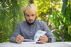 De jonge boeken van de de mensenlezing van de hipsterbaard in huistuin met aard stock afbeelding