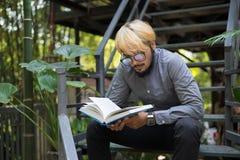 De jonge boeken van de de mensenlezing van de hipsterbaard in huistuin met aard stock foto's