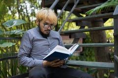 De jonge boeken van de de mensenlezing van de hipsterbaard in huistuin met aard royalty-vrije stock afbeeldingen