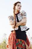 De jonge boervrouw, kleedde zich in Hongaars nationaal kostuum, dat over aardachtergrond stelt Royalty-vrije Stock Foto's